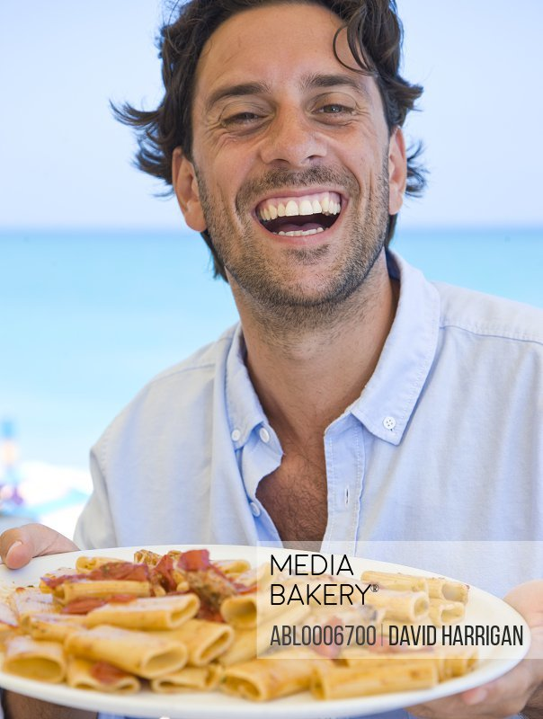 Smiling Man Holding Plate of Ciavattoni Pasta