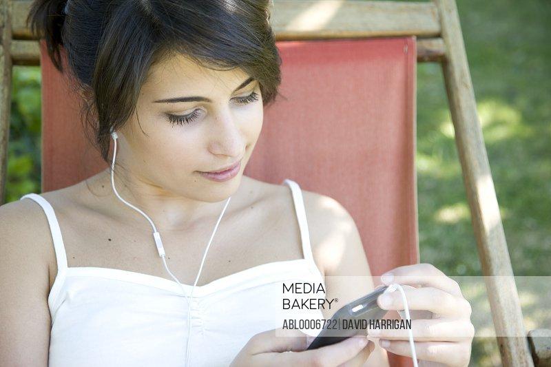 Woman Wearing Headphones Holding Smartphone