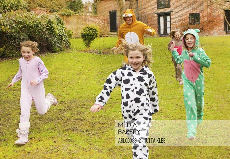 Man and Girls Wearing Animal Costumes Running in Garden