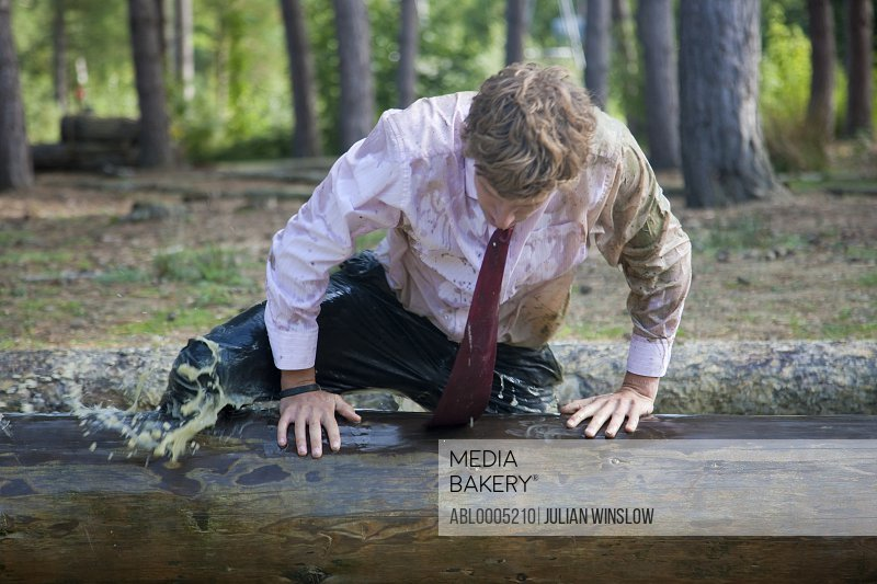 Businessman at obstacle course clambering over a wooden beam soaked in muddy water