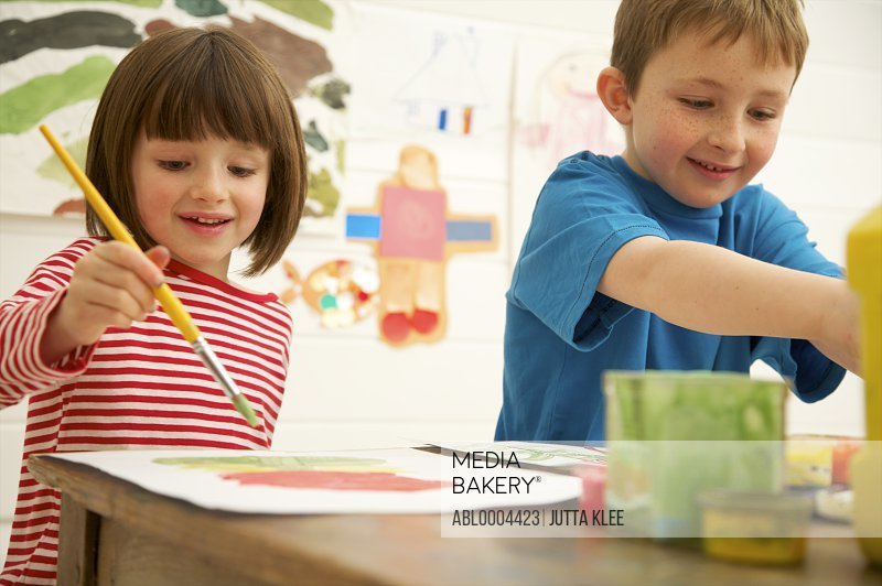 Portrait of a boy and young girl painting and smiling