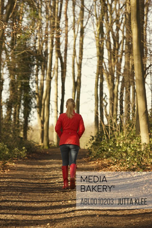 Back View of Woman Walking in Forest Path