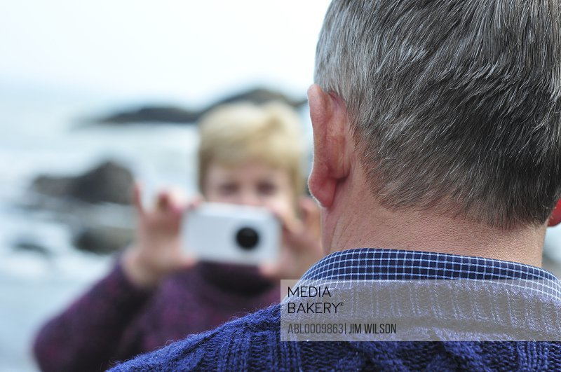 Woman Taking Photo of Man with Smart Phone
