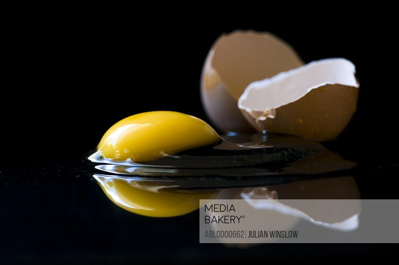 Broken egg on black background