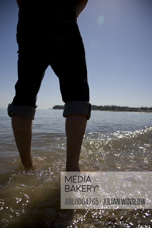 Man legs with rolled up trousers standing in the shoreline