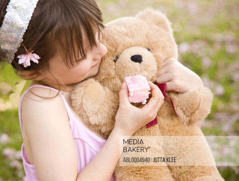 Young girl holding and feeding cake to a teddy bear