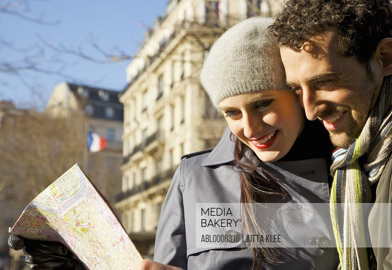 Couple looking at map, Paris, France