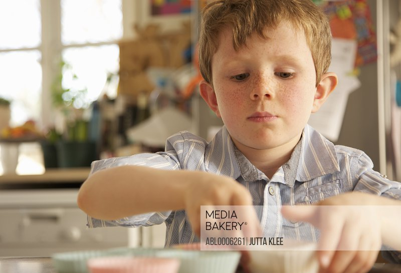 Young boy positioning cupcakes cases