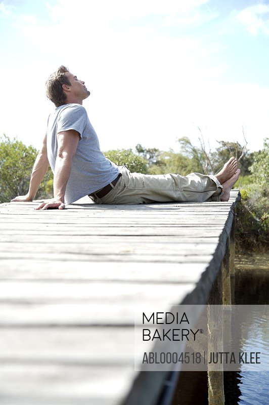 Portrait of barefoot man sitting on a boardwalk by a river