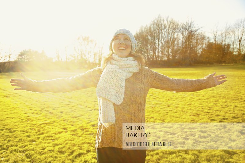 Woman Standing in Field with Arms Outstretched Smiling