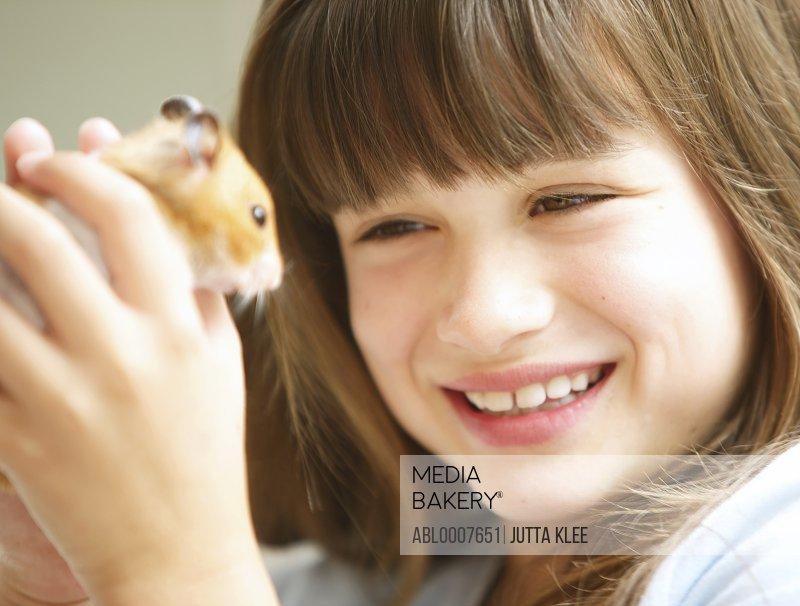 Smiling Girl Holding Hamster