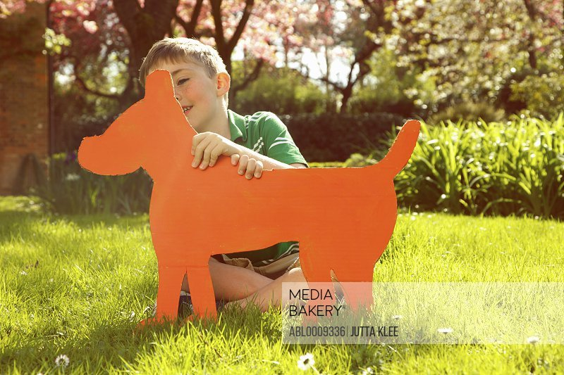 Young Boy Holding Cardboard Cut Out in Shape of Dog