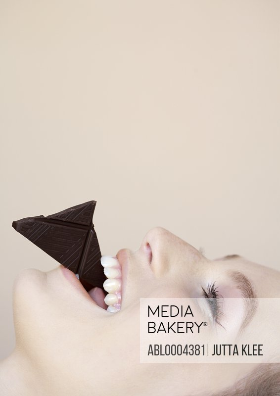 Close up profile of beautiful young woman eating chocolate