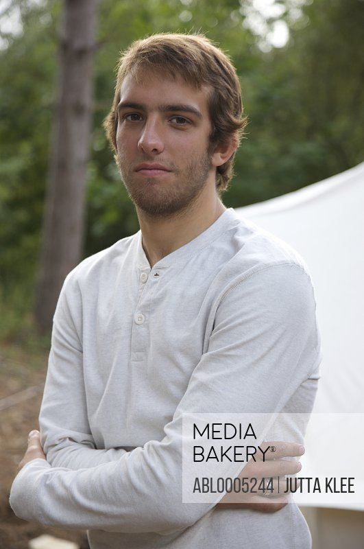 Young man standing by a tent with his arms crossed