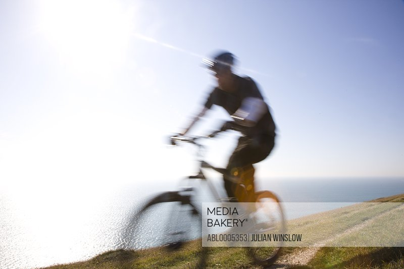 Man cycling on a costal path by the ocean
