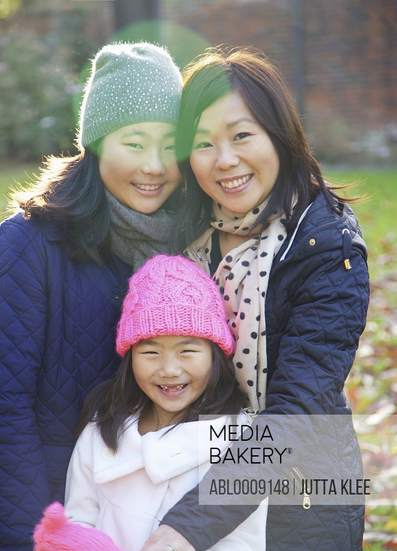 Mother and her Daughters Smiling Outdoors
