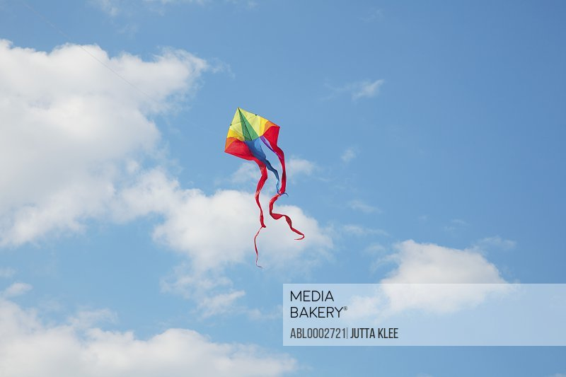 A Kite Flying in a Cloudy Blue Sky