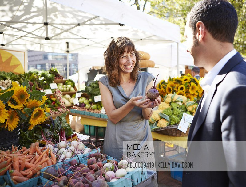 Smiling Woman Holding a Red Beet