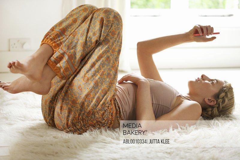 Young Woman Lying on Rug Using Smartphone