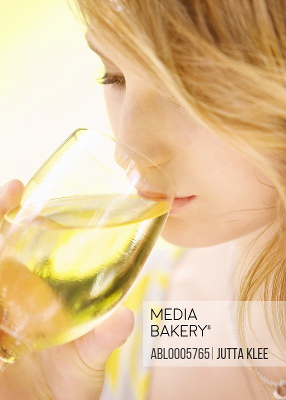 Young woman drinking white wine