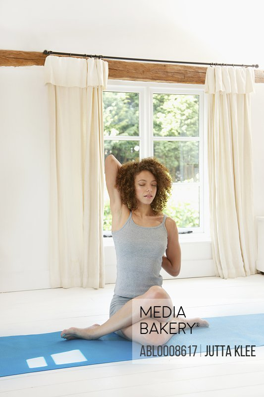 Woman Practicing Yoga in the Cow Face Pose