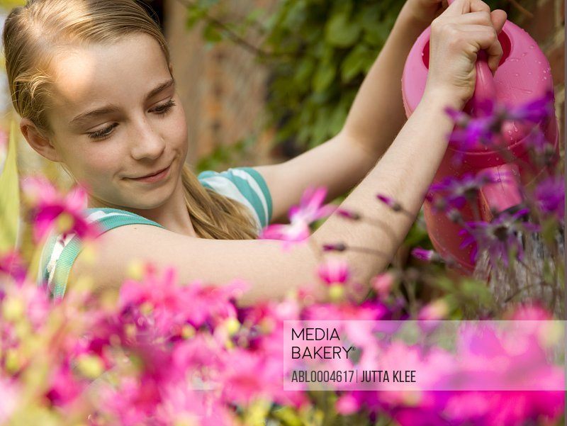 Portrait of a girl watering flowers with pink watering can