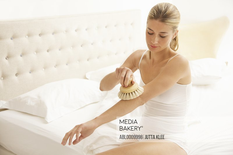 Woman Sitting on Bed Exfoliating her Arm