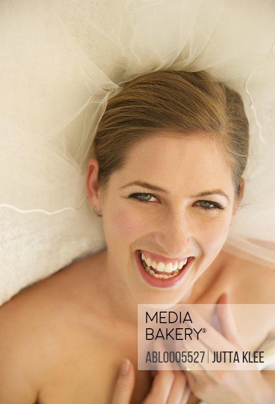 Smiling bride lying on her back