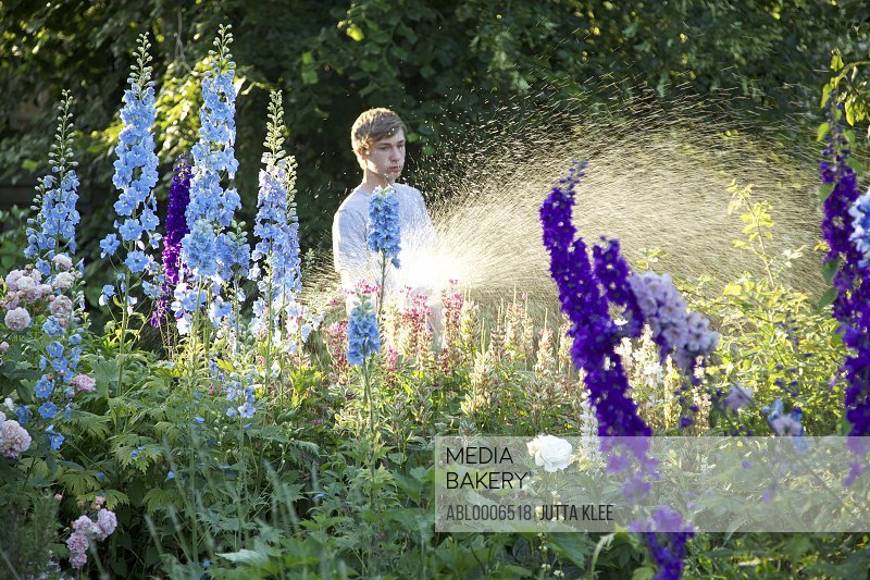 Teenage Boy Watering Flowers with Garden Hose