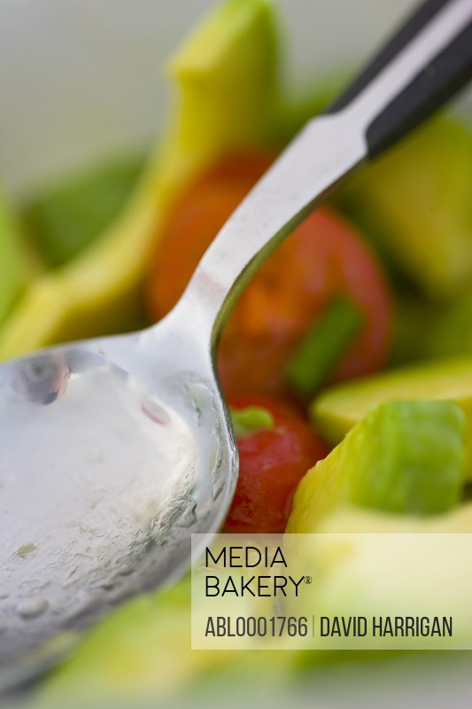 Extreme close up of a spoon and tomato and avocado salad