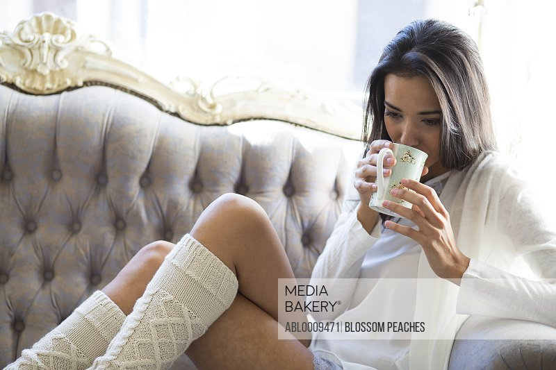 Woman Sitting on Sofa Sipping Hot Drink