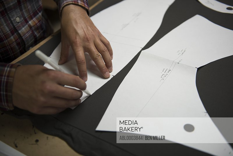 Man Outlining Sewing Pattern on Wet Suit Fabric