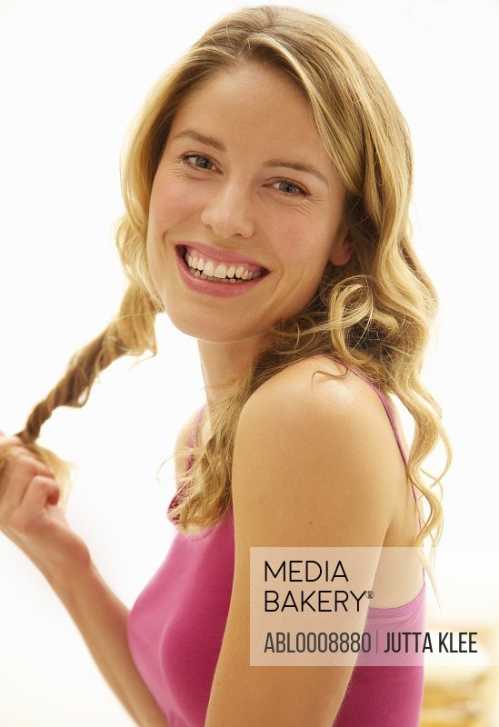 Smiling Woman Twisting Strand of Hair