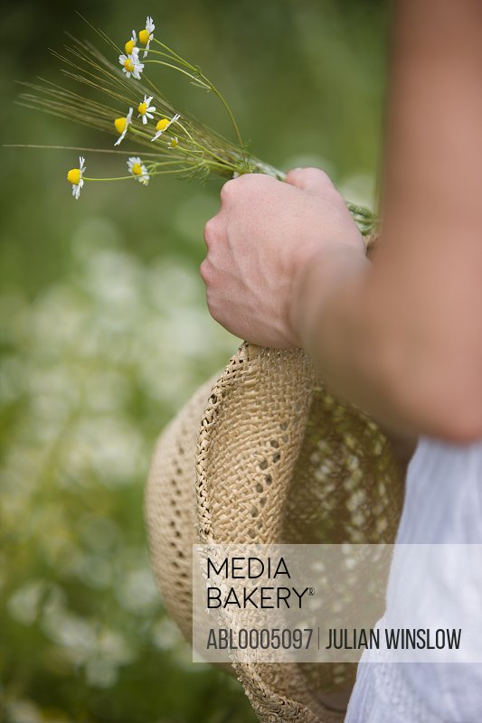 Close up of a woman hand holding a straw hat and camomile flowers