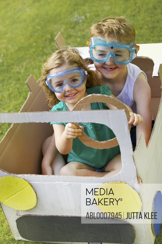 Boy and Girl Wearing Goggles Driving Cardboard Car