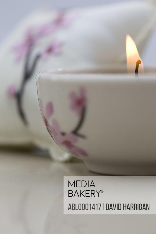 Close up of a burning pink tea light and matching cushion
