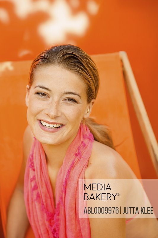 Woman on Orange Deck Chair Smiling