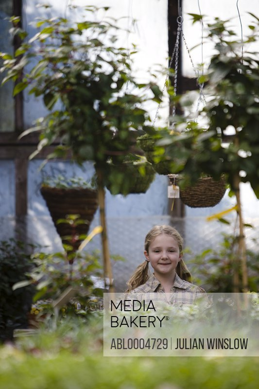 Young girl in a nursery standing under hanging baskets smiling