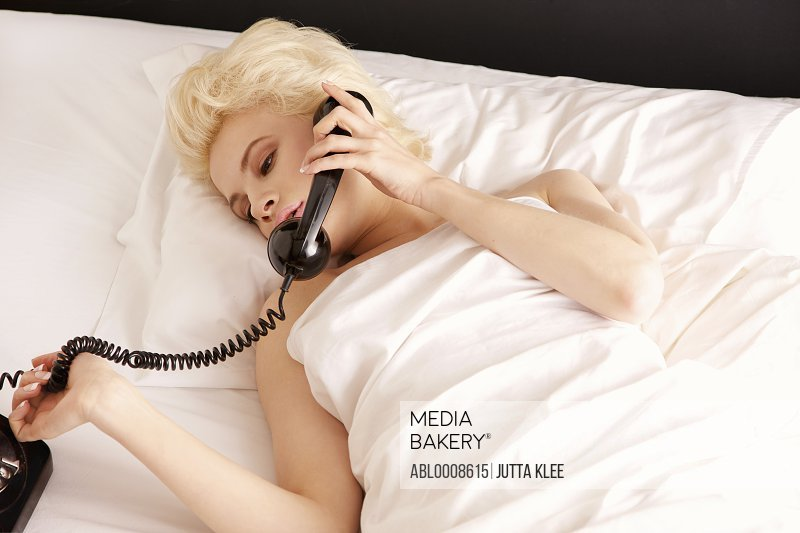 Young Woman Lying in Bed Using Old-Fashioned Telephone