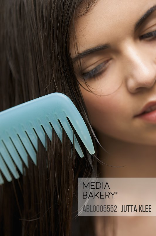 Extreme close up of a woman combing her hair with a wide tooth comb