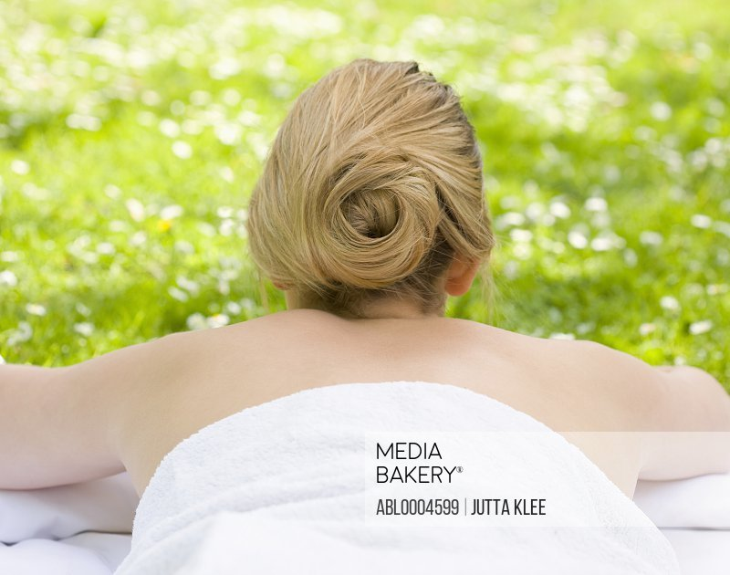 Back view of woman lying on stomach on the grass wrapped in a towel