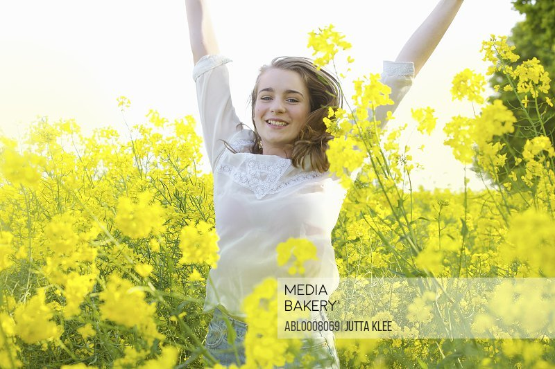 Smiling Teenage Girl with Arms Raised amongst Canola Flowers
