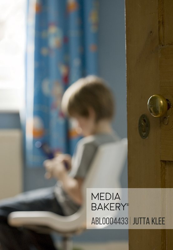 Portrait of young boy sitting text messaging on cell phone with bedroom door detail