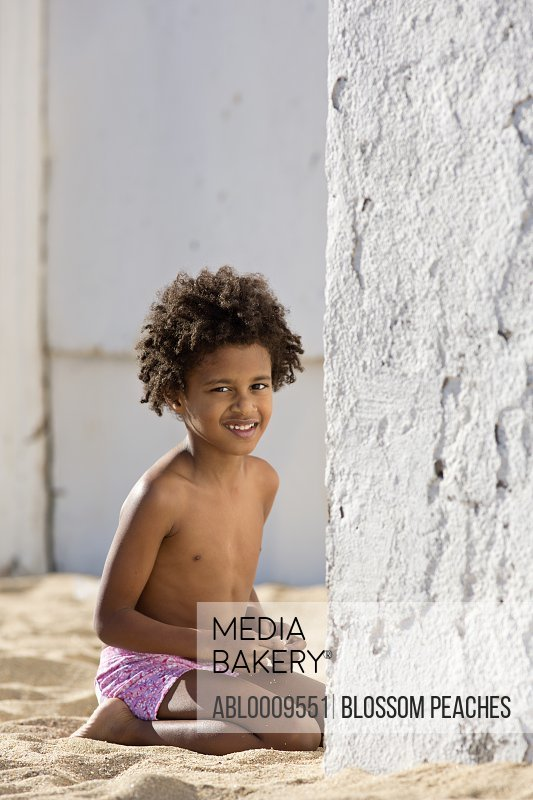 Boy Kneeling on Sand next to Wall Smiling
