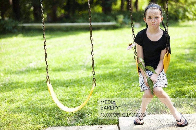 Girl Sitting on Swing Holding Flower