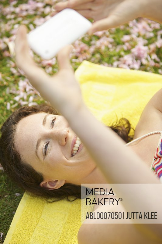 Young Woman Lying on Grass Holding Smartphone above her Face