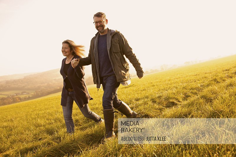 Smiling Couple Walking in a Field Holding Hands