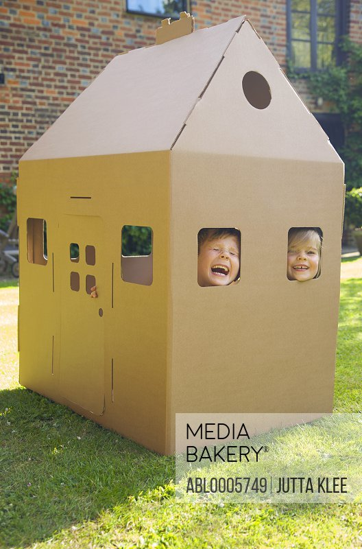 Boy and girl looking out from the windows of a cardboard playhouse laughing and screaming