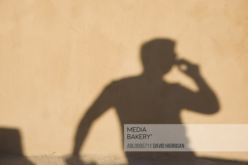 Shadow on a wall of a man using a cell phone