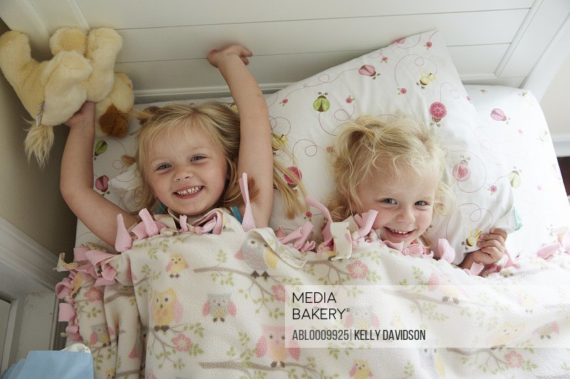 Two Young Girl Lying in Bed Smiling